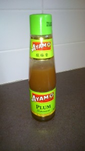 "A bottle of ""Ayam"" plum sauce. The sauce is a light brown colour."